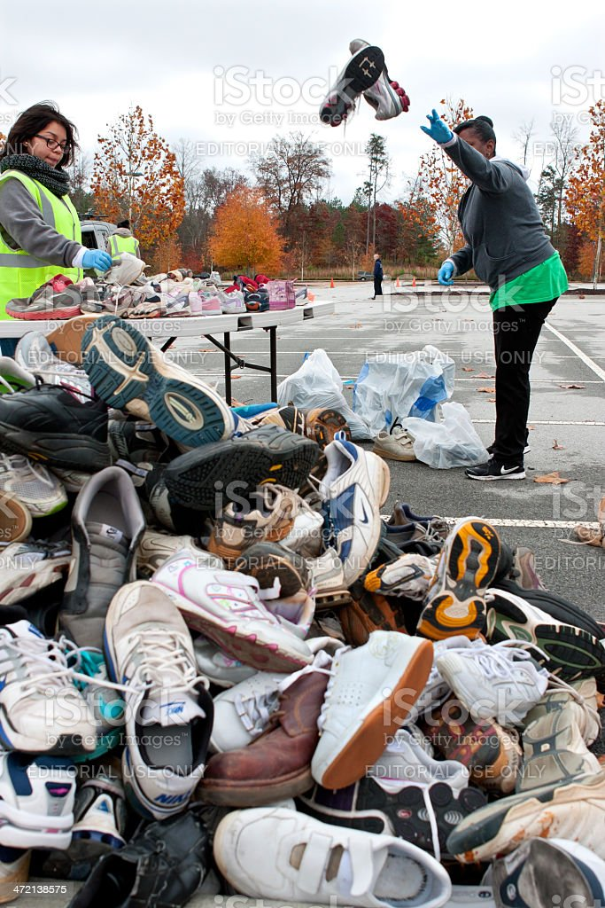 Volunteer Tosses Sneakers Into Shoe Pile At Recycling Event stock photo