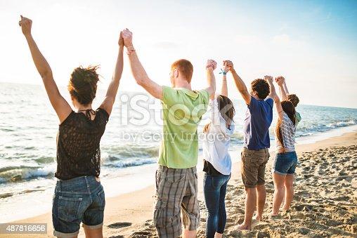 istock volunteer with arm raised at sunset 487816656