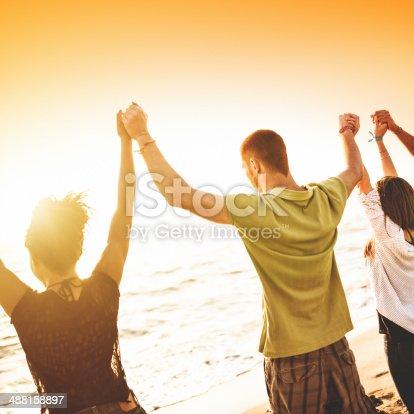 istock volunteer with arm raised at sunset 488158897