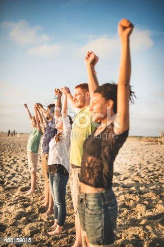 istock volunteer with arm raised at sunset 488159015