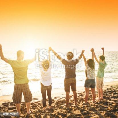 istock volunteer with arm raised at sunset 488159019
