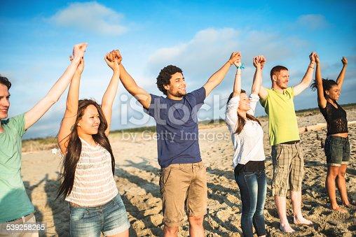 istock volunteer with arm raised at sunset 539258265