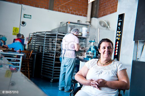 594475880istockphoto Volunteer with disability working at Bakery Workshop 618457010