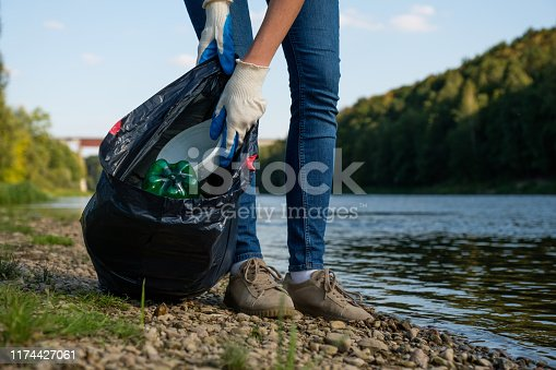istock Volunteer woman collecting plastic rubbish on coast of the river. Cleaning environment concept 1174427061