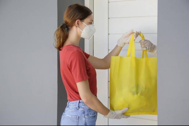 Freiwillige Frauen bringen eine Tüte mit Lebensmitteln und ein weiteres unessesary Lebensmittel für Menschen in Not. Lieferung an die Tür. Lebensmittellieferdienste während der Coronavirus-Pandemie. – Foto