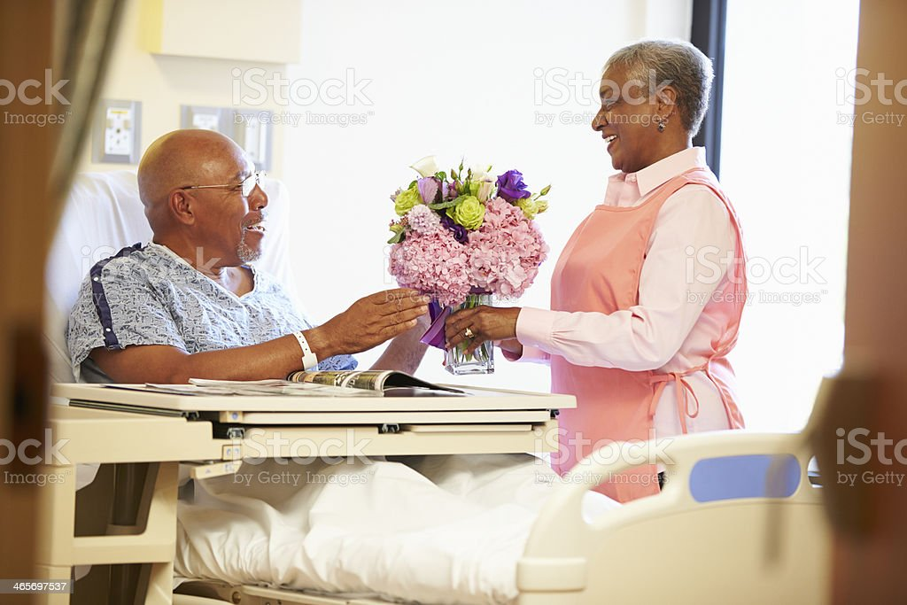 Volunteer Worker Tidying Male Patient's Hospital Room stock photo