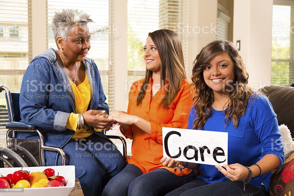 Volunteerism:  Young adults visit senior woman in nursing home. royalty-free stock photo