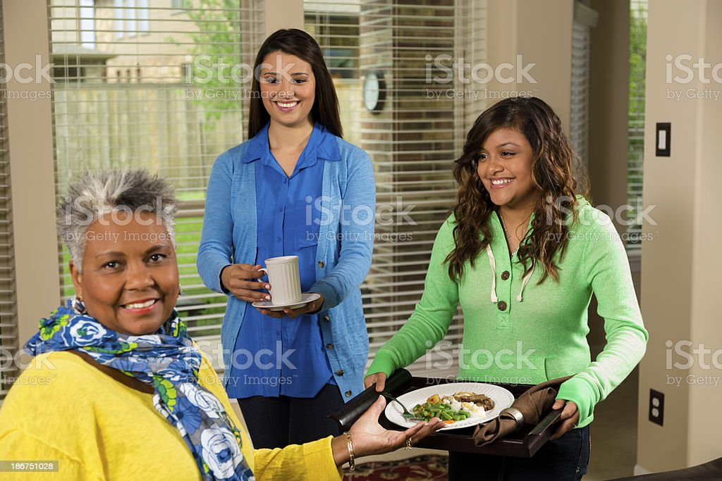 Volunteerism: Young people provide meal to senior woman. stock photo