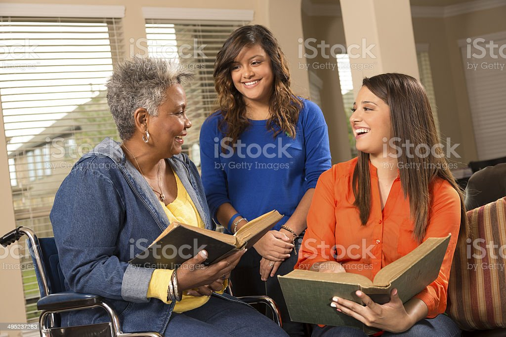 Volunteerism: Young women read to senior woman. House, nursing home. stock photo