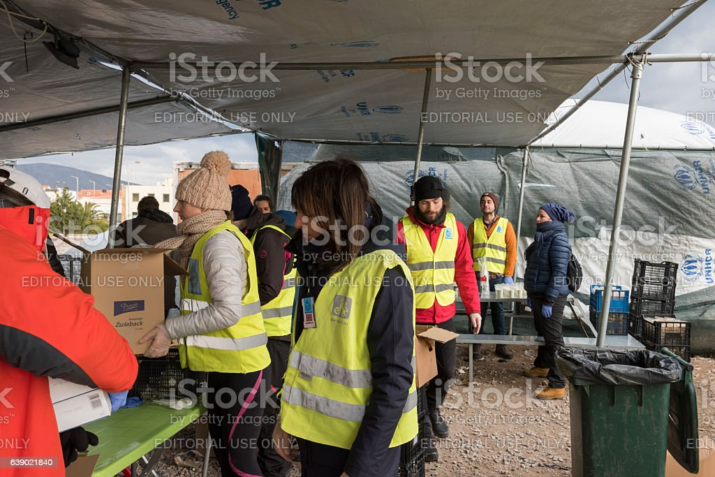Volunteers are distributing breakfast in Greek refugee camp at Christmas royalty-free stock photo