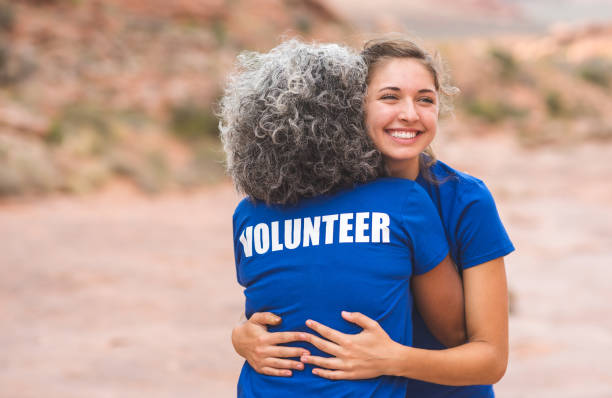 Volunteers at Utah Desert Race Two volunteers give each a hug before the big event - a race in the desert. The shot is over the shoulder of a senior ethnic woman and is focused on a smiling Caucasian millennial-age woman. environmental consciousness stock pictures, royalty-free photos & images
