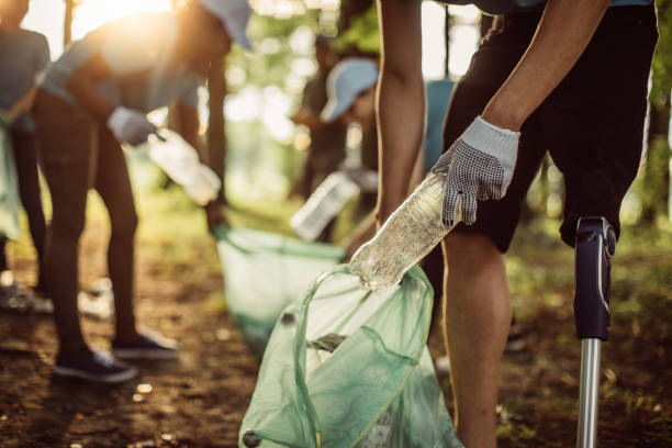 Volunteers cleaning park Group of multi-ethnic people, people with differing abilities , volunteers with garbage bags cleaning park area environment stock pictures, royalty-free photos & images