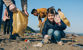 Little happy girl with volunteers picking up trash on the beach