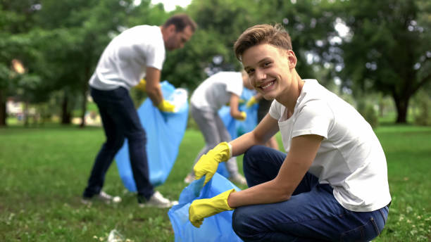 Volunteers collect litter, teenager smiling, environmental and ecological care Volunteers collect litter, teenager smiling, environmental and ecological care environmental consciousness stock pictures, royalty-free photos & images