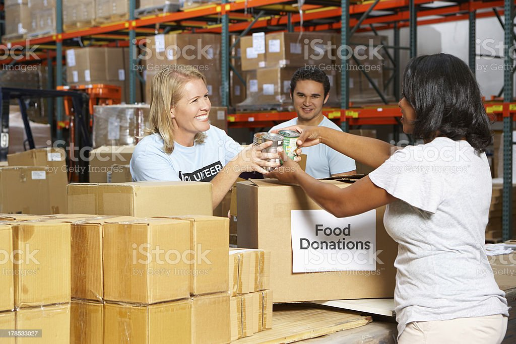 Volunteers Collecting Food Donations In Warehouse stock photo