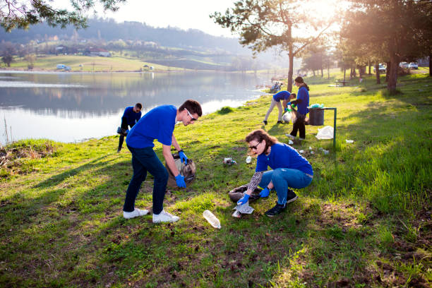 Volunteers collecting garbage People cleaning up litter next to the lake social responsibility stock pictures, royalty-free photos & images