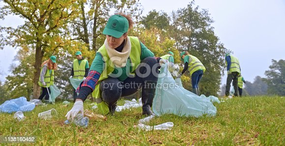 Local cleanup volunteers collecting plastic bottles and rubbish in park.