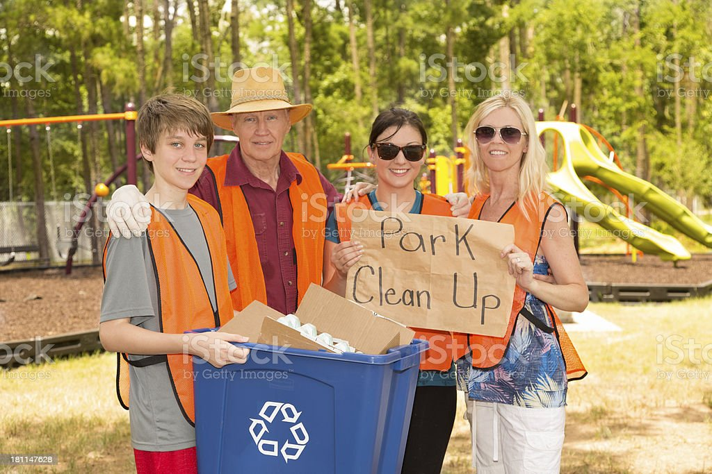 Volunteers: Family holds Park Clean Up sign. Environmental awareness royalty-free stock photo