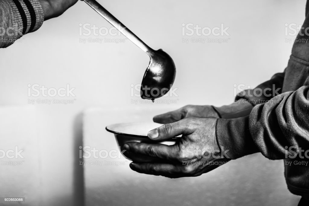 Volunteers feed the homeless. Free soup in a bowl of beggar. stock photo