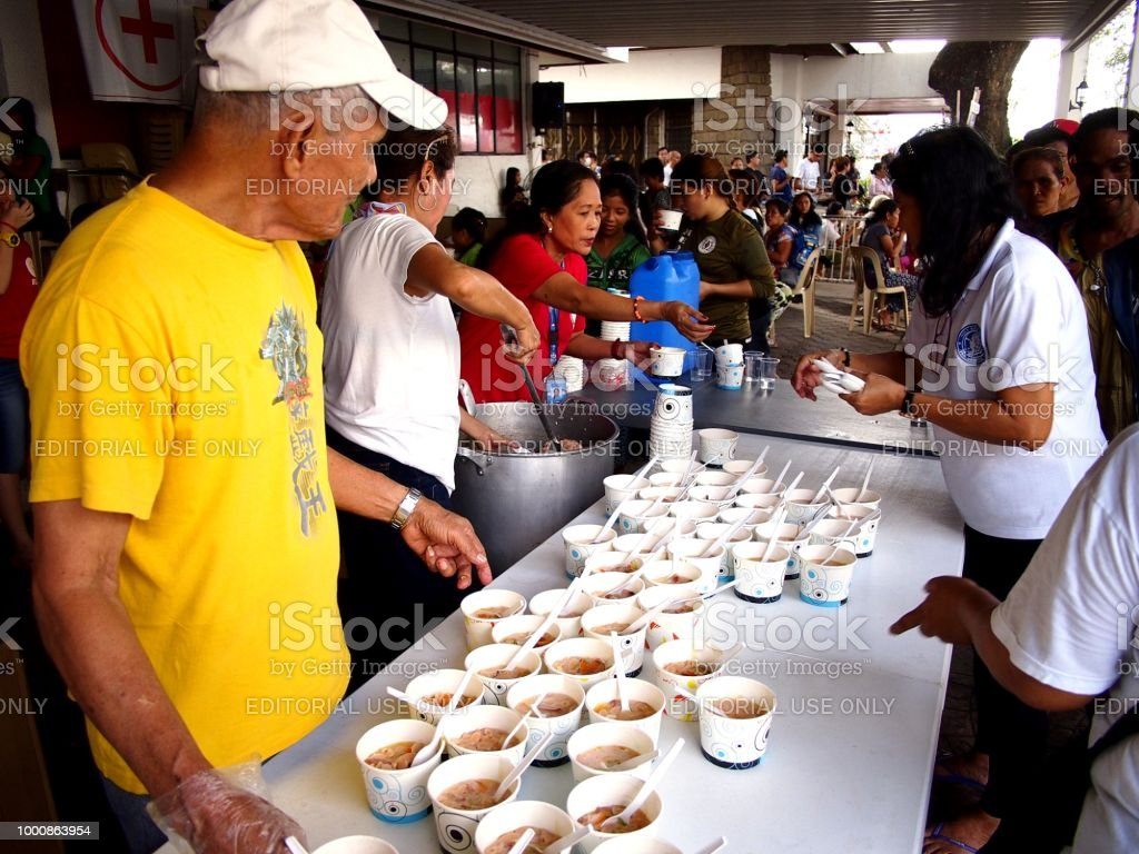 Volunteers give out food during a feeding program at a church. stock photo