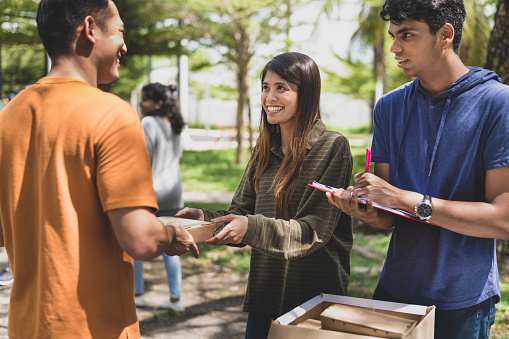 A group of helpful volunteers arranging and packing cardboard boxes with free meals and give away to any needy families and local community facing financial difficulty during an outdoor charity food drive.