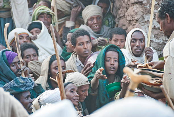 Volunteers hand out food to pilgrims after Christmas, Lalibela, Ethiopia. stock photo