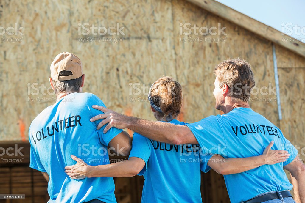 Volunteers helping to build homes for the needy stock photo