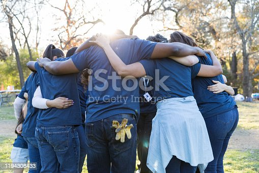 Unrecognizable group of volunteers huddle together after a successful community cleanup event.