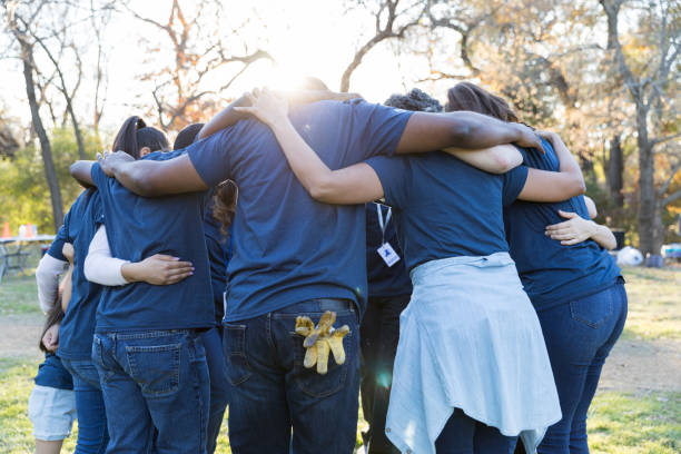 Volunteers huddle together during community cleanup day stock photo
