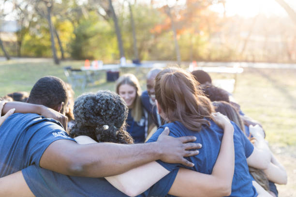 Volunteers huddle together, showing unity Unified group of neighbors come together to cleanup their neighborhood. They are huddled together with their arms linked. social responsibility stock pictures, royalty-free photos & images