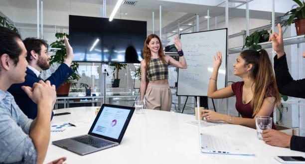 Volunteers in business team meeting, hands raised stock photo