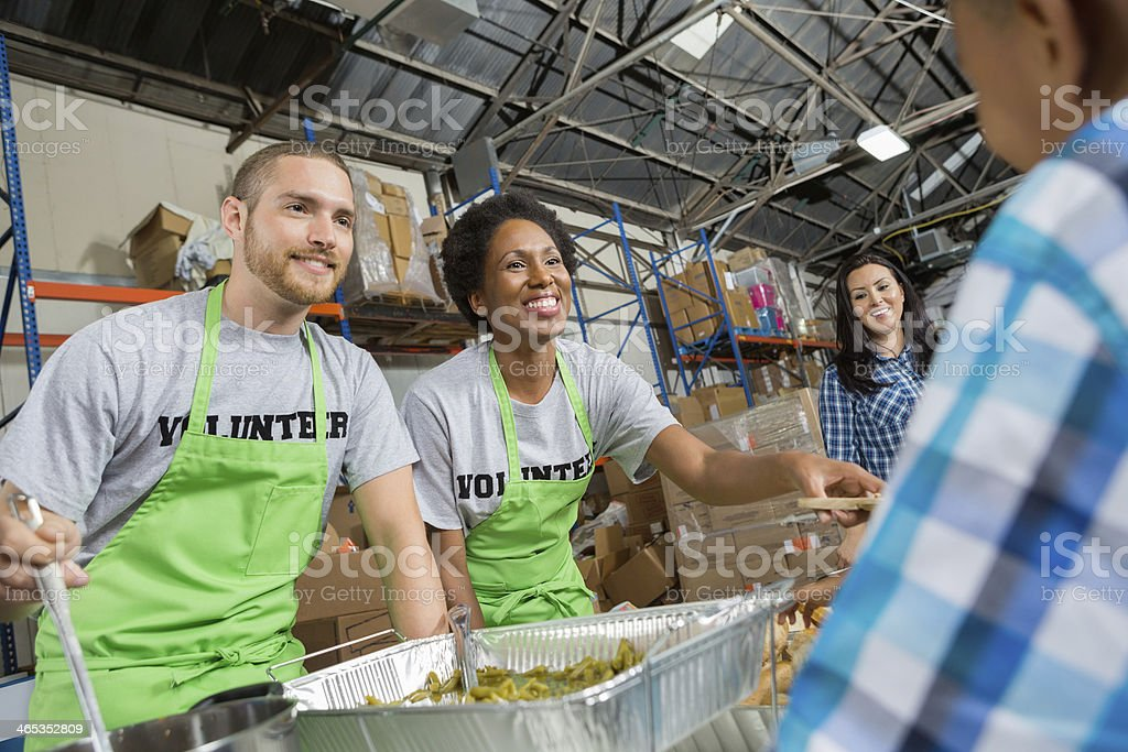 Volunteers in community soup kitchen serving hot meal to families stock photo