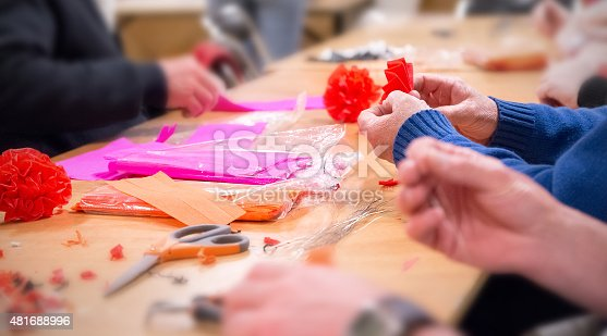 istock Volunteers manufacture colored crepe paper decorations on table 481688996
