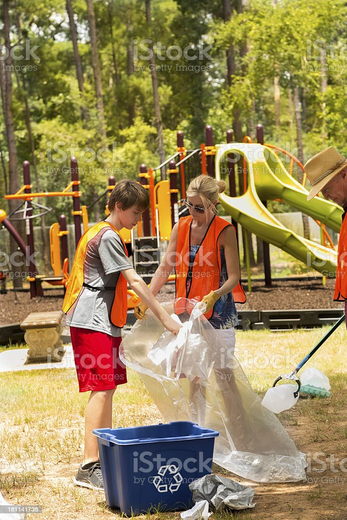 Volunteers: Mom and son clean littered park for recycling. Environment royalty-free stock photo