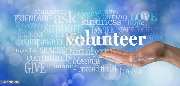 Male hand palm up with the word 'volunteer' floating above surrounded by a relevant word cloud on a blue bokeh background