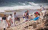 Bonaire 05-07-2019: volunteers cleaning up the oilpatches which has washed up ashore after flooting around in the ocean
