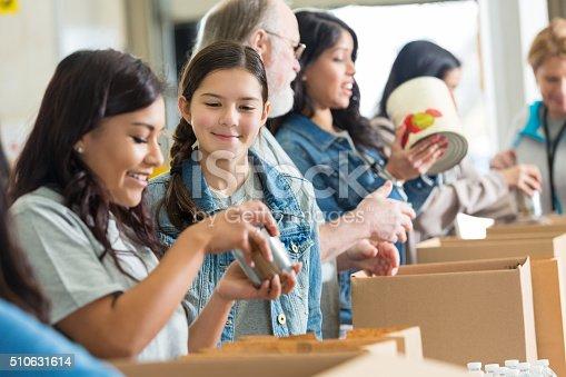 istock Volunteers pack canned food in community food drive 510631614