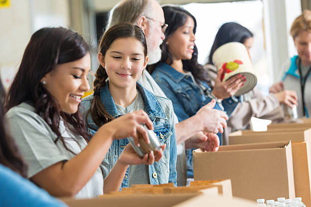 Volunteers pack canned food in community food drive stock photo