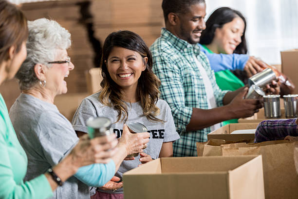 volunteers pack canned goods into boxes during food drive - community project stock photos and pictures