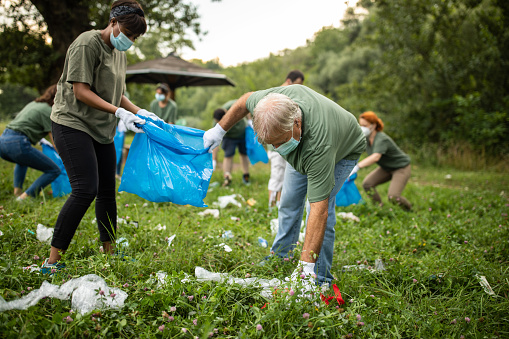 Volunteers picking up garbage while cleaning public park during covid-19 pandemic
