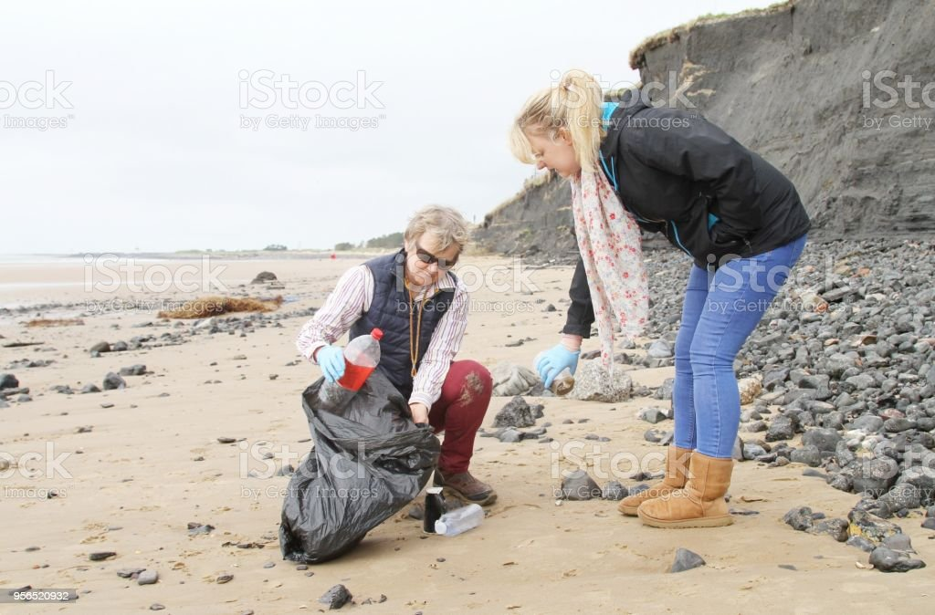 volunteers picking up plastic rubbish on beach stock photo