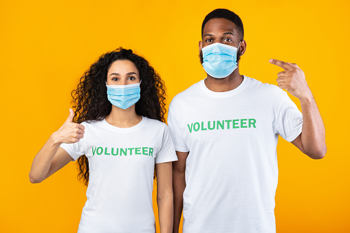 Volunteers Pointing Fingers At Masks Gesturing Thumbs-Up Over Yellow Background