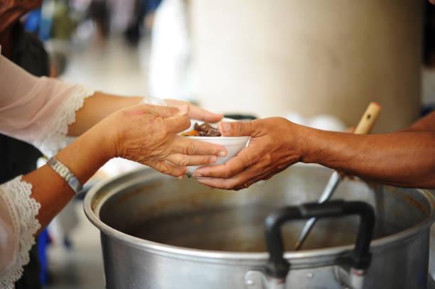 Freiwillige versorgen Bettler mit Lebensmitteln: Konzepte füttern und helfen: Die Hände der Reichen geben Nahrung für die Armen – Foto
