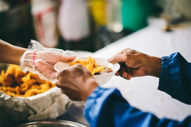 Freiwillige, die das Essen ausschöpfen, um sie mit den Bedürftigen zu teilen: Konzept der Bereitstellung kostenloser Lebensmittel für Obdachlose. – Foto