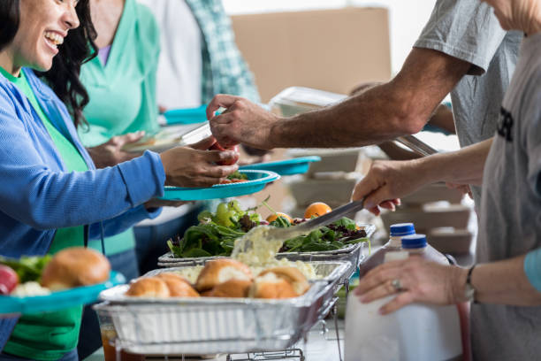 Volunteers serve people in soup kitchen stock photo