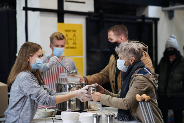 Volunteers serving hot soup for homeless in community charity donation center, coronavirus concept. stock photo