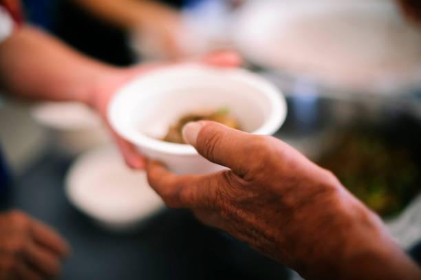 Ehrenamtliche teilen Essen an die Armen: Hands-on-Essen der Hungernden ist die Hoffnung auf Armut: Begriff Obdachlosigkeit – Foto