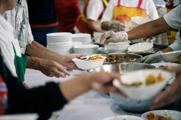 freiwillige anteil essen für die armen zur linderung des hungers: charity-konzept - wohltätigkeit und humanitäre hilfe stock-fotos und bilder