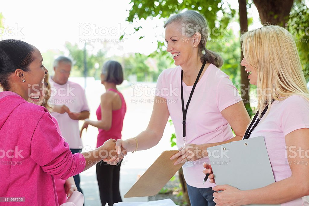 Volunteers signing up ladies for breast cancer awareness race royalty-free stock photo