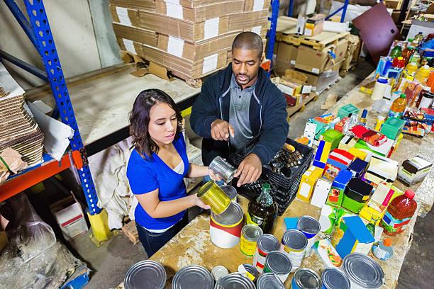 volunteers sorting las donaciones en un banco almacén de distribución de alimentos - ayuda humanitaria fotografías e imágenes de stock